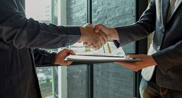 Businessman shakehand and exchanging contract documents.