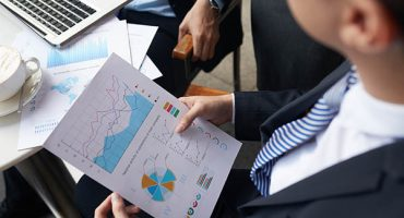 Report with financial statistics in hands of buisnessman who is meeting with colleague